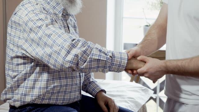 vídeos de stock, filmes e b-roll de massagista examina a dor no pulso e cotovelo de um velho - punho