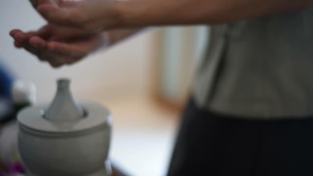 vidéos et rushes de un masseur est mettre de l'huile dans sa main et se frotter les mains ensemble avant de faire l'huile de massage. - salons et coiffeurs
