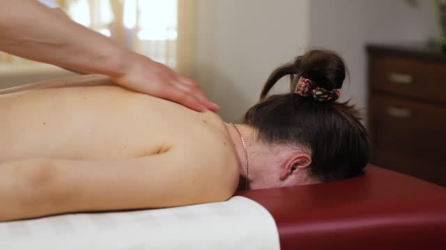 vídeos y material grabado en eventos de stock de masajista hace masaje médico de espalda - espalda humana