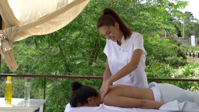 vídeos y material grabado en eventos de stock de masajista haciendo un masaje a una mujer irreconocible acostado - tratamiento de spa