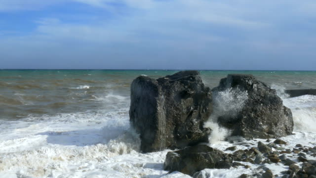 Massive boulders on beach during storm, close-up video