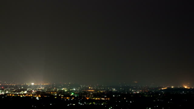 Massive colorful cloud to ground lightning bolts hitting the horizon of city lights. video