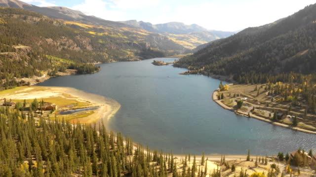 vídeos de stock, filmes e b-roll de massive lake escondido entre as montanhas por drone - condado de pitkin
