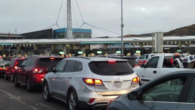 massiva linjer av bilar som väntar på att korsa in i usa från mexiko vid san ysidro international crossing i tijuana - ram bildbanksvideor och videomaterial från bakom kulisserna