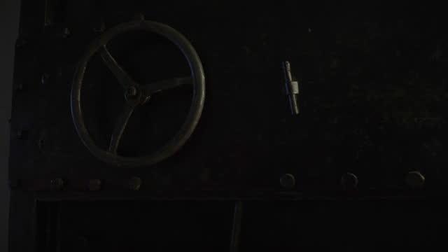 Massive metal door with round wheel. Huge safe storage or bank vault. Massive metal door with round wheel. Huge safe storage or bank vault. safes and vaults stock videos & royalty-free footage