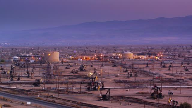 stockvideo's en b-roll-footage met massale olieveld met verlichte raffinaderij bij zonsondergang - drone shot - olieraffinaderij