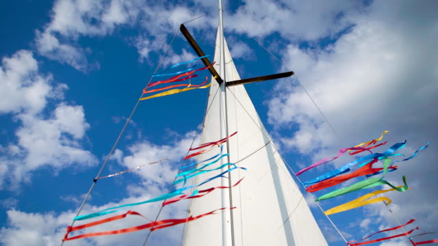 vídeos de stock e filmes b-roll de mast, white sail and multicolor tapes of sailing boat are on background of bright blue sky with white clouds - regata