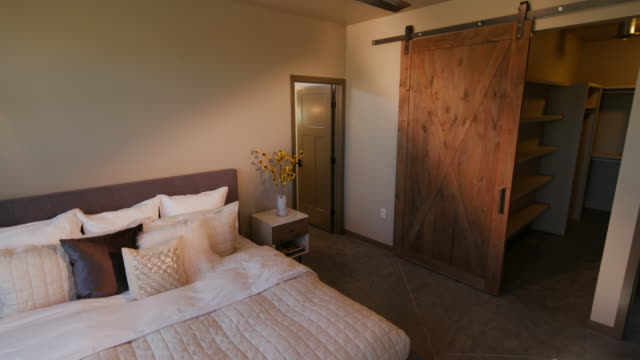 master bedroom lowering with barn door walk in closet - bedroom video stock e b–roll