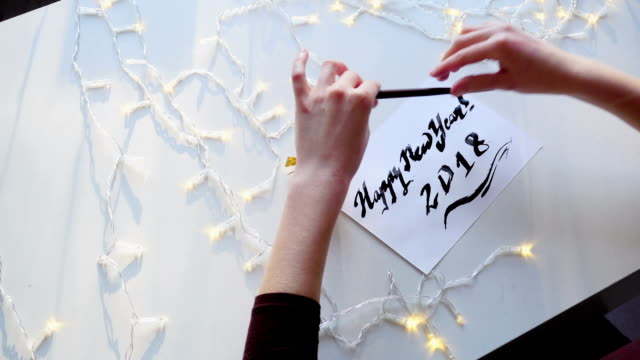 vidéos et rushes de maître calligraphe finitions dessin carte de vœux avec de l'encre sur la feuille de papier, assis à table avec guirlande en atelier - carte postale
