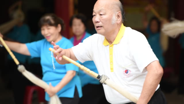 Master demonstrates TaiChi movement for seniors practicing