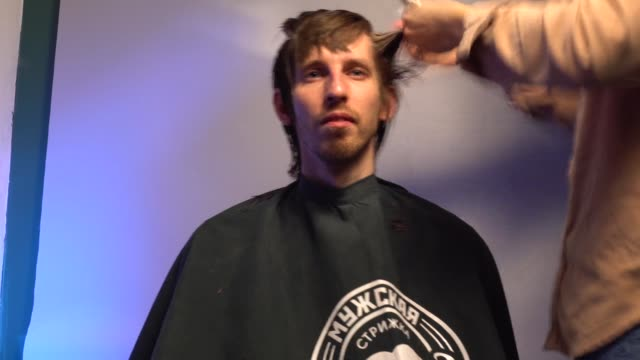 master hands hold instruments and perform hairstyle for guy. timelapse video