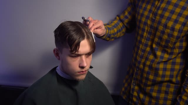 master hands hold instruments and perform hairstyle for guy video