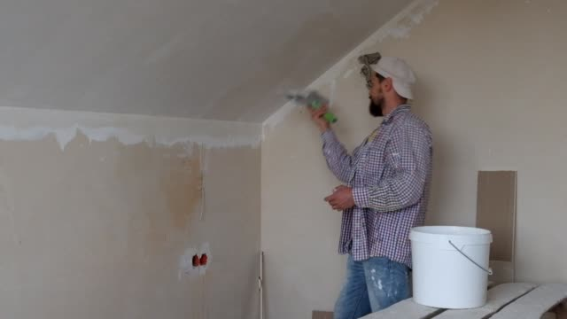 Master in a plaid shirt applying putty on putty knife and plastering a wall with finishing putty video
