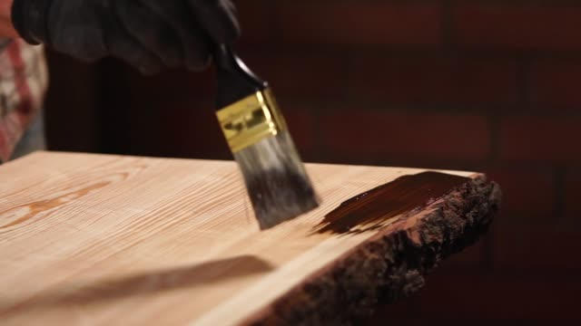 Master is applying a paint in broad strokes on a wooden board in a factory Worker is painting wooden details in factory of producing furniture. Hand of man with brush is applying drying oil painting art product stock videos & royalty-free footage