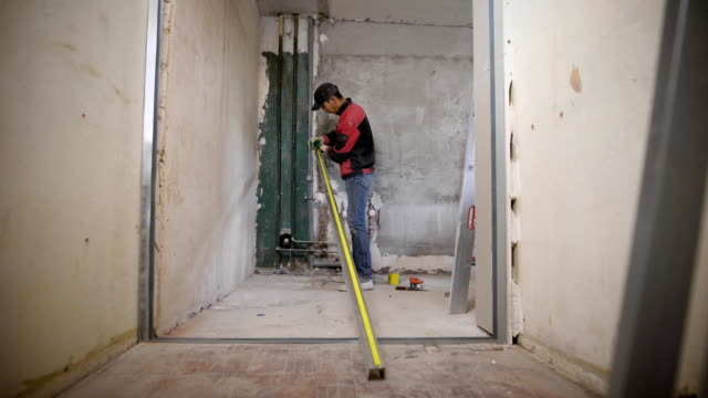 master is measuring long aluminum profile by tape-measure and making marks on it, standing in a repairing flat video