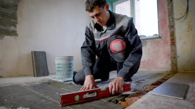 master is wearing work clothes, is checking horizon of installing tiles, using building level, adjusting video