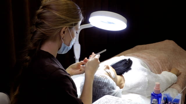 Master makes eyelash extension to client in beauty shop video