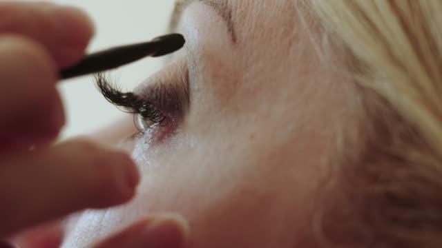 master make-up artist apply professional make-up eyes in a beauty salon to a woman model with gray eyes closeup. - wschodnio europejski filmów i materiałów b-roll