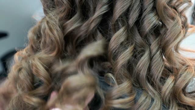 stockvideo's en b-roll-footage met meester maken van kapsel voor de bruinharige meisje - curly brown hair