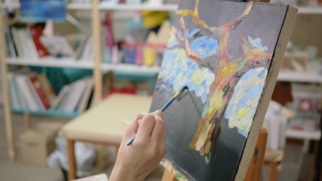 Master of painting is making strokes on picture in studio, close-up
