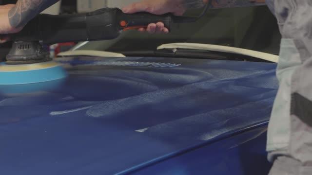 meister poliert der tiefblaue sportwagen über polnisch mashine in einer autowerkstatt - wachs epilation stock-videos und b-roll-filmmaterial