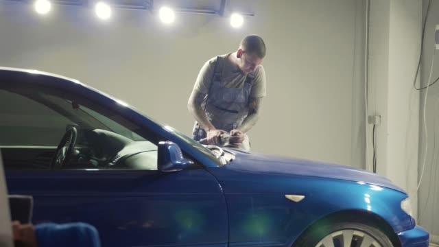 Master polishes the deep blue sport car via polish mashine in a car workshop video