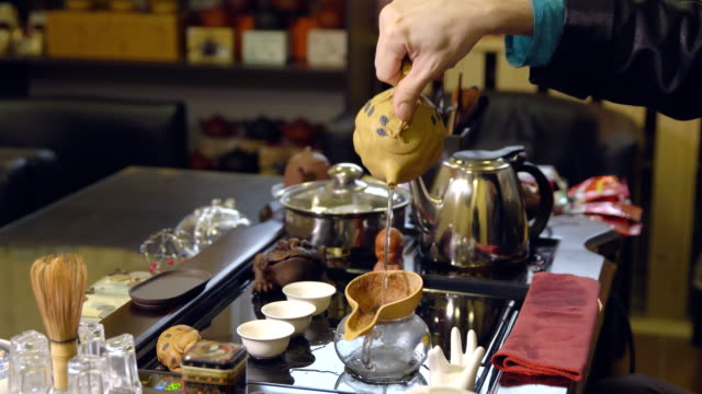 master pours tea leaves with water. tea ceremony - teapot stock videos & royalty-free footage