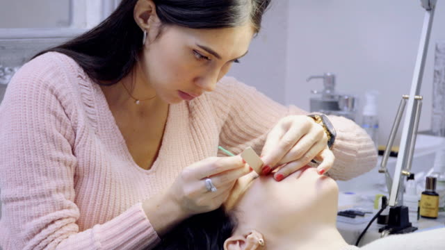 vídeos de stock e filmes b-roll de master removes old false eyelashes and prepares patient to eyelash extension - cílio