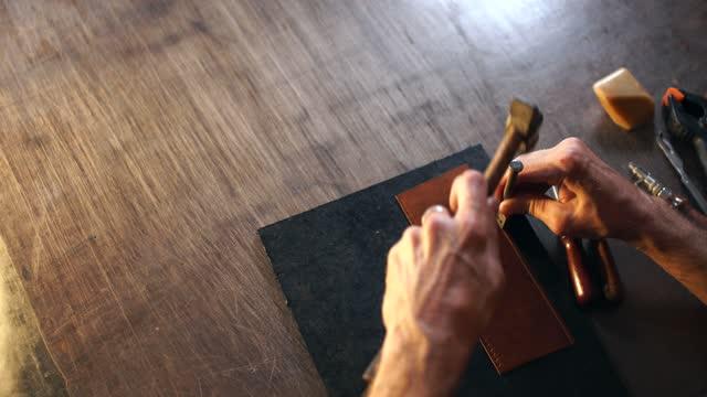 vídeos de stock e filmes b-roll de master tanner works with skin in leather workshop. - fundo oficina