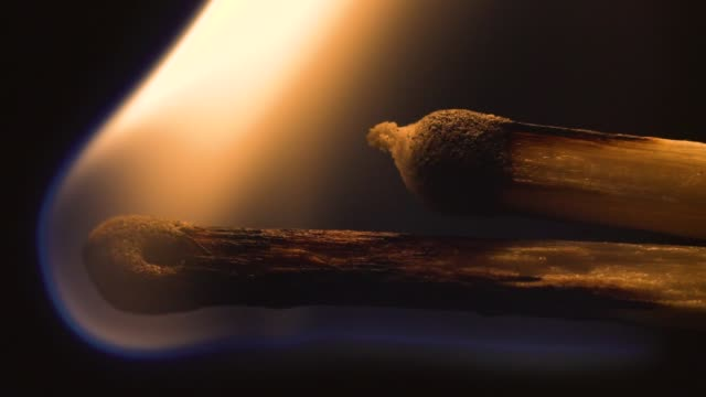 Match inginiting burning extreme macro close up background. Macro extreme close up shot of a wooden match igniting after being heated up,and bursting into flames burning till the end. Slow motion