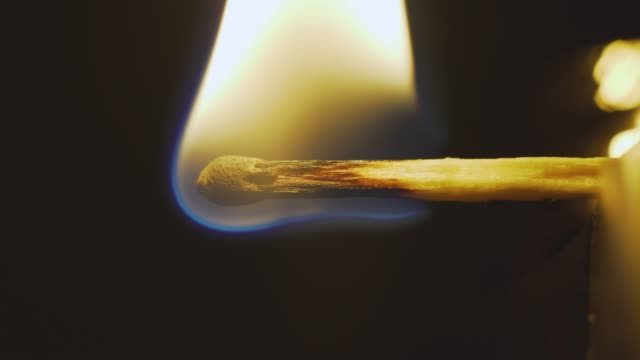 Match inginiting burning extreme macro close up background. Macro extreme close up shot of a wooden match igniting after being heated up,and bursting into flames burning till the end.