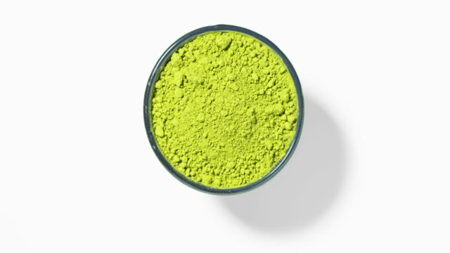 vídeos y material grabado en eventos de stock de té verde matcha en tazón de fuente redondo sobre fondo blanco, lazo - molido