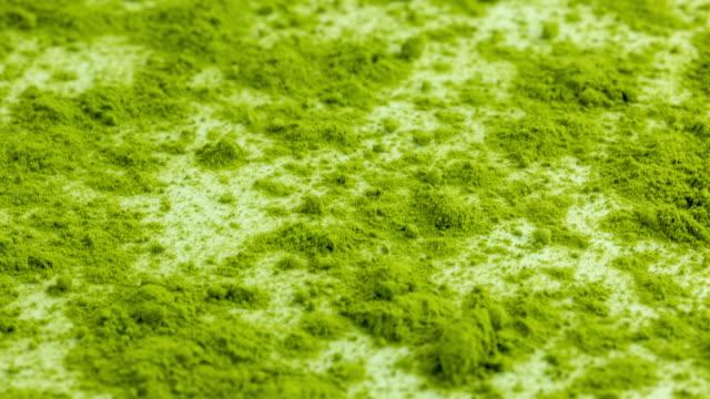 matcha tee boden auf weißem hintergrund - grüner tee stock-videos und b-roll-filmmaterial