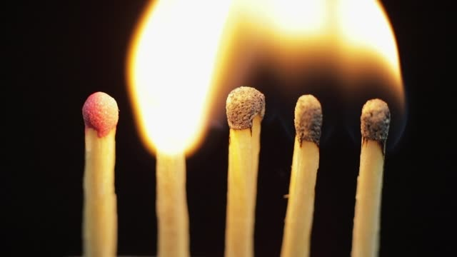 Matches light up one by another in series on black background