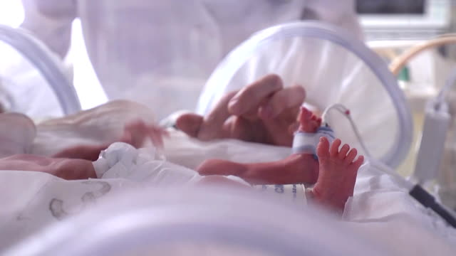 Maternity centre. .Severely ill newborn in incubator, intensive hospital therapy: CCU, ICU, ITU. The tiny baby child moves his fingers, foot and leg vigorously. Close up. Medical room with a newborn baby lying in a box, incubator. hd