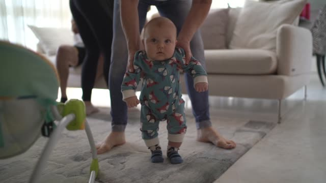 Mather helping son learn to walk at home