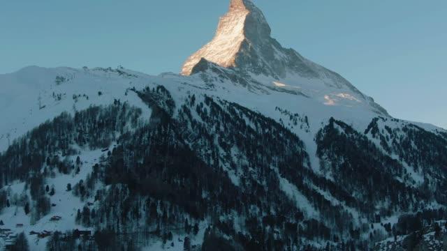 vidéos et rushes de matterhorn mountain et forest en hiver matin. alpes suisses. suisse. vue aérienne. tir moyen - inclinaison vers le haut