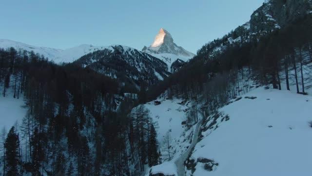 stockvideo's en b-roll-footage met matterhorn berg en bos in de winter 's ochtends. zwitserland. luchtfoto - zermatt