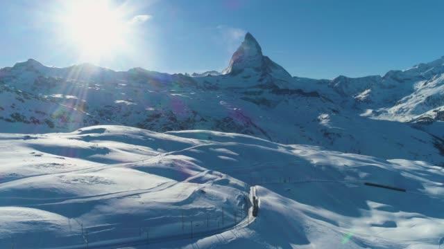 stockvideo's en b-roll-footage met matterhorn mountain en trein in zonnige winter dag. zwitserse alpen. zwitserland. luchtfoto. onthullen shot - matterhorn