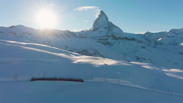 stockvideo's en b-roll-footage met matterhorn mountain, gornergrat trein en zon in de winter bij zonsondergang. zwitserland. luchtfoto - zermatt
