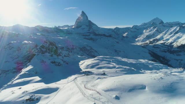 stockvideo's en b-roll-footage met matterhorn mountain in zonnige winter dag. zwitserse alpen. zwitserland. luchtfoto. onthullen shot - matterhorn