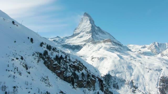 stockvideo's en b-roll-footage met matterhorn mountain in de winter dag. zwitserse alpen. zwitserland in de sneeuw. luchtfoto. medium shot - zermatt