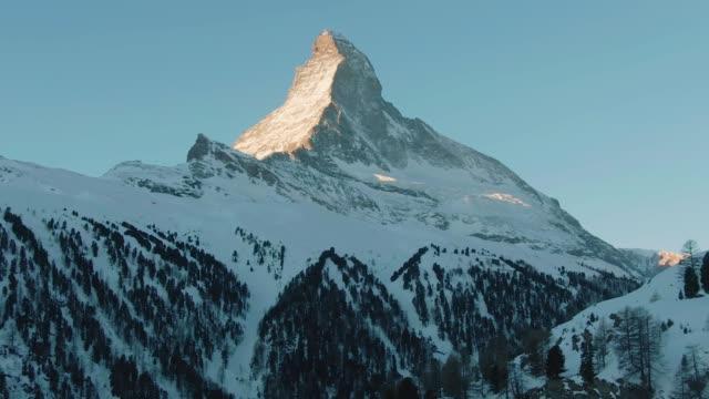 stockvideo's en b-roll-footage met matterhorn mountain in de winter zonnige ochtend bij zonsopgang. zwitserse alpen. zwitserland. luchtfoto - matterhorn