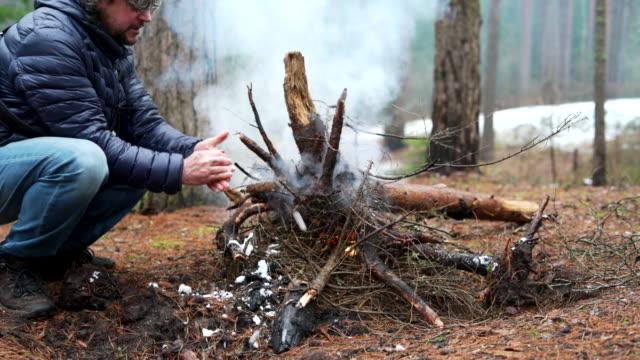 olgun 45-yıl-yaşlı adam tarafından kış orman yangın bir kar ile el yıkama. - şömine odunu stok videoları ve detay görüntü çekimi
