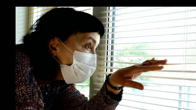 Mature adult brunette woman caucasian ethnicity, in medical mask opening blinds.