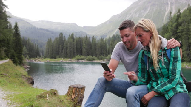 Mature adult couple by lake looking at smart phone video