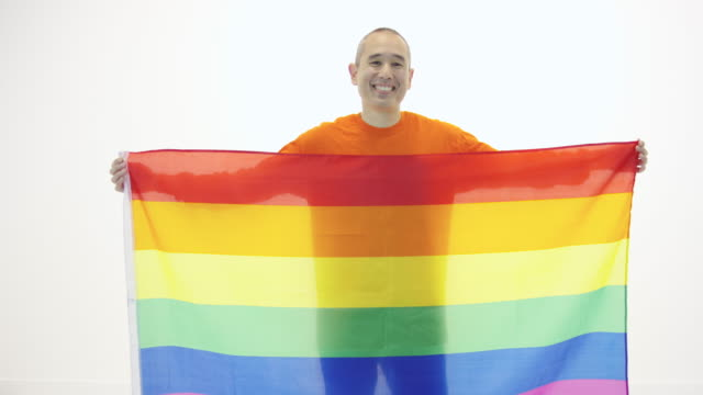 Mature adult holding gay pride flag against white backdrop video