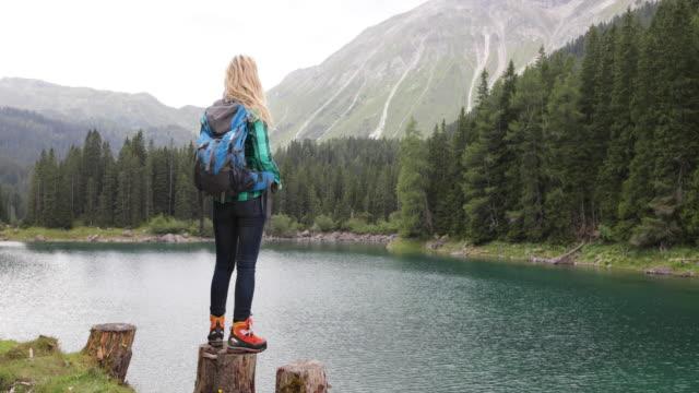 vídeos de stock, filmes e b-roll de mulher adulta madura pelo lago, apreciando a paisagem de natureza cênica - tyrol state austria