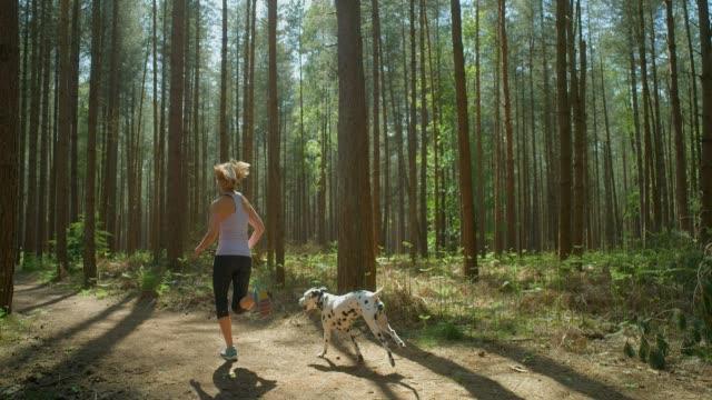 Eine reife erwachsene Frau, die mit ihrem dalmatinischen Hund läuft. – Video
