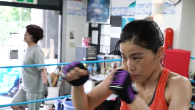 成熟した大人の女性ボクシング ジムでトレーニング - ボクシング点の映像素材/bロール